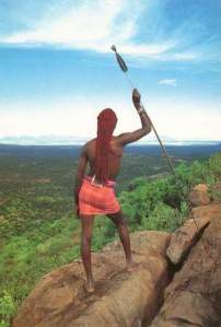 maasai worrior viewing the Great Rift Valley on a rock on the escarpment. Source: Postcard, Westland Sundries, Nairobi